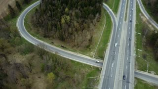 Aerial drone view of the traffic countryside roadway near the green forest. Cars drive through the fork.