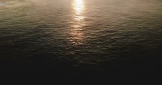Aerial shot of epic sunset reflection in ocean water surface, camera tilt up to reveal amazing tropical coast skyline.