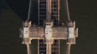 Aerial top view of Brooklyn bridge in New York, America. Drone flying over the East river and traffic road.