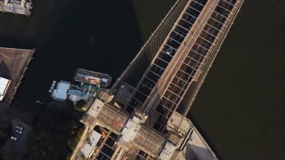 Aerial top view of Brooklyn bridge, with American flag on it. Scenic view of East river in New York, America.