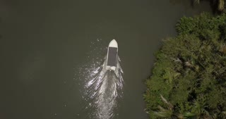 Aerial top view of little white fisherman boat sailing along beautiful jungle river with sun reflections in rainforest.
