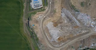 Aerial top view of the garbage dump and waste management plant. Copter flying over the big pile of trash.