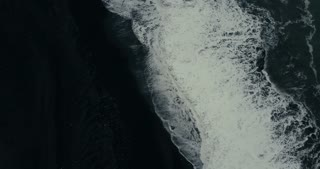 Aerial top view of the powerful wave with foam coming on the shore of black volcanic beach in Iceland.