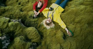 Aerial top view of the two happy woman lying on the soft moss in lava field in Iceland. Tourists resting on nature.
