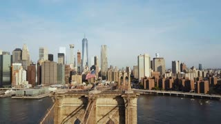 Aerial view of Brooklyn bridge with American flag waving on the wind. Scenic view of East river, Manhattan in New York.