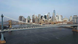 Aerial view of downtown in New York, America. Drone flying over Manhattan bridge and under Brooklyn bridge, acceleration