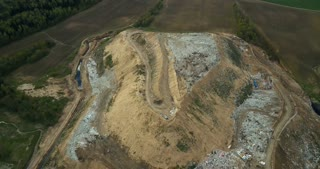 Aerial view of garbage dump and waste management plant. outside the city. Copter moves around the big pile of trash.