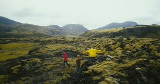Aerial view of group of tourists hiking on lava fields in Iceland. Woman photographer holding camera, waiting friends