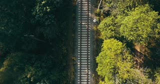 Aerial view of man running up on train track. Vertical drone view. Concept of chasing dreams and surviving life trials.