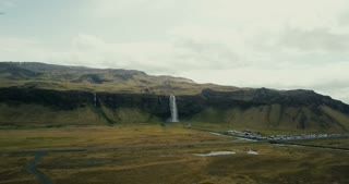 Aerial view of mountains valley and Seljalandsfoss waterfall. Copter flying over the famous touristic place in Iceland.