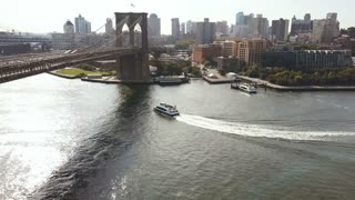 Aerial view of New York, America. Drone flying over the East river, boat riding through the water, under Brooklyn bridge
