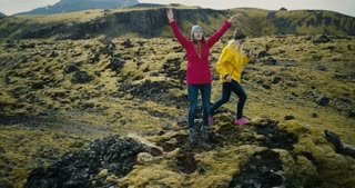 Aerial view of the beautiful landscape in Iceland, lava field covered moss. Two woman dance and jump on the mountain.