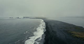 Aerial view of the black volcanic beach in Iceland. Copter flying over the beautiful shore of the sea with waves.