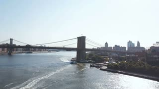 Aerial view of the Brooklyn bridge through the East river from Brooklyn district. Drone flying over the traffic road.