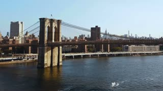 Aerial view of the Brooklyn bridge through the East river on Manhattan, New York. Drone flying over the traffic road.