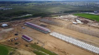 Aerial view of the countryside. Building construction of agronomic industry, warehouse in the field.