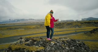 Aerial view of the friends standing on the top of mountain and dancing of happiness. Two woman in lava field in Iceland.