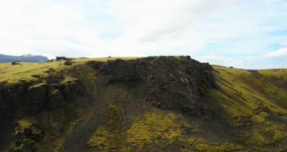 Aerial view of the green lava field with bumps covered moss. Drone flying over the mountains and cliffs in Iceland.