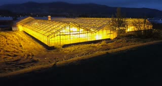 Aerial view of the greenhouse in the night. Copter flying over the agriculture farm, field with plants.