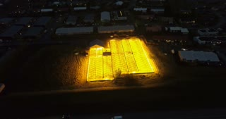 Aerial view of the greenhouse with bright light shining inside the building. Natural agricultural fields.