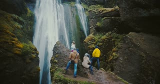Aerial view of the group of tourist resting on the top of mountain and looking on the Gljufrabui waterfall in Iceland.