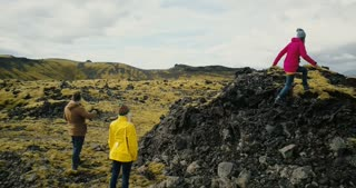 Aerial view of the group of tourists hiking on lava field in Iceland. Two woman raise hands up, feel happy and freedom.