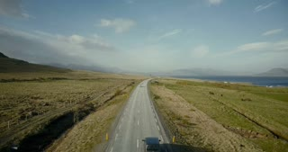 Aerial view of the mountains road. Cars riding through the green field on the motorway near the shore of the sea.