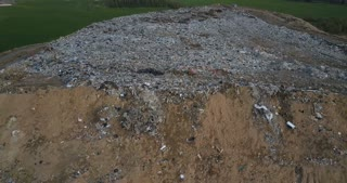 Aerial view of the pile of trash. Copter flying away from the urban dump outside the city, big pile of dirty waste.