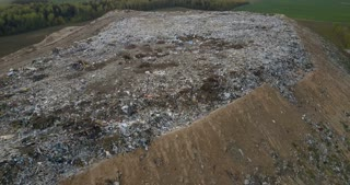 Aerial view of the pile of trash. Copter flying over the urban dump outside the city, refuse dirty waste.