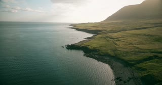 Aerial view of the shore of the sea in sunny day. Copter flying over the green meadow in bright summer day in Iceland.