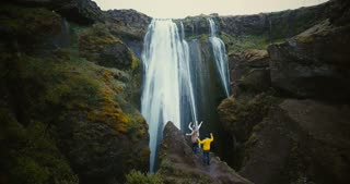 Aerial view of the tourist looking on Gljufrabui waterfall in Iceland. Group of people enjoying the scenic landscape.