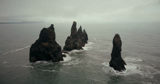 Aerial view of the troll toes mountains on the sea in Iceland. Flock of seagulls making nests on the cliffs.