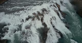 Aerial view of the turbulent flow of water in the cliffs. Copter flying over the powerful waterfall in Iceland.