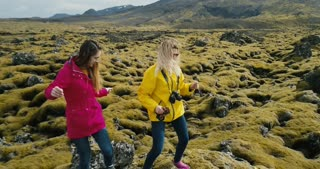 Aerial view of the two happy woman standing on the rock and having fun, dancing. Lava field in Iceland covered moss.