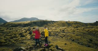 Aerial view of the two woman in the lava field in Iceland raise hands. Happy tourists send air kiss to copter.