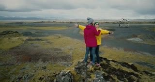 Aerial view of the two woman standing on the top of mountain covered moss and hugging. Tourists in lava field in Iceland
