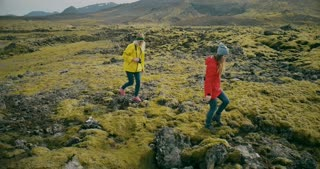 Aerial view of the two woman walking on the lava field in Iceland together. Tourists touches the moss bumps.