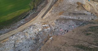 Aerial view of the urban dump and waste recycling factory. Copter flying over the big piles of garbage trash.