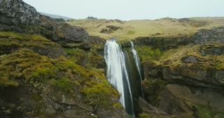 Aerial view of the waterfall Gljufrabui in Iceland. Copter flying over the green valley and river falling down.