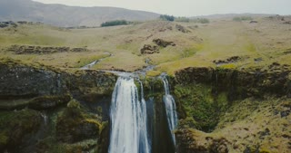 Aerial view of the waterfall Gljufrabui in Iceland. Copter moves down, group of people standing on the top of mountain.