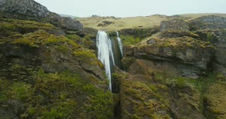 Aerial view of the waterfall Gljufrabui in mountain in Iceland. Copter flying near the turbulent flow falling down.