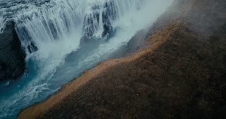Aerial view of the waterfall Gullfoss in cleft. Copter flying over the valley and turbulent flow in Iceland.
