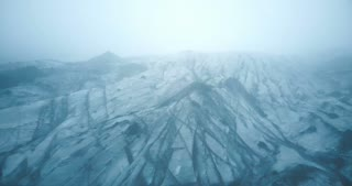 Aerial view of the white glacier Myrdalsjokull with black ash in Iceland. Copter flying over the iceberg in the fog.
