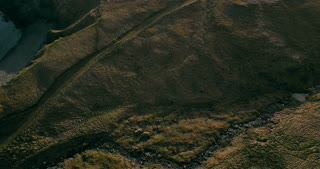 Aerial view of the wild river flows in the valley. Copter flying over the green fields. Lava mountains in Iceland.