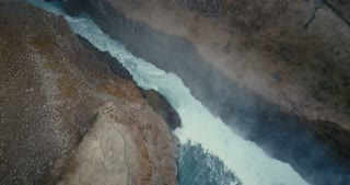 Aerial view of the wild river in mountains crevice. Beautiful waterfall Gullfoss in Iceland, turbulent flow.