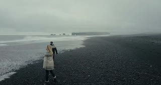 Aerial view of the young couple walking on the black volcanic beach in Iceland. Woman in lopapeysa jumps on the man arms