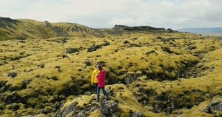 Aerial view of tourists woman standing on the rock on lava field in Iceland. Female use the smartphone in nature.