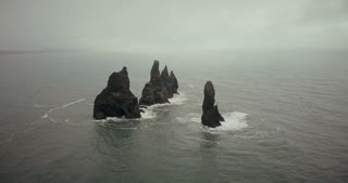 Aerial view of troll toes mountains on the water in Iceland and flock of birds on it. Beautiful landscape of sea and fog