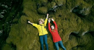 Aerial view of two happy tourists woman lying on the lava field in Iceland. Copter flies up from close-up to long shot