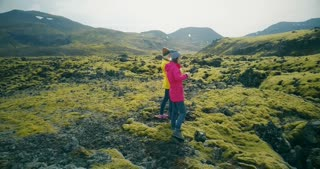 Aerial view of two tourists woman walking on lava fields in Iceland and making photos. Girls use smartphone and camera.